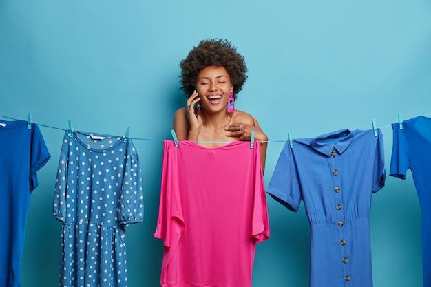 Concepto de mujer, estilo y moda. mujer afroamericana adulta llena de alegría tiene conversación telefónica, posa desnuda detrás de un vestido de noche rosa colgando de una cuerda