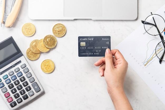 Concepto de una mujer que realiza pagos en línea con tarjeta y teléfono inteligente aislado en una mesa de oficina de mármol moderna, maqueta, vista superior, espacio de copia, endecha plana, de cerca