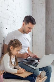 Concepto multitarea, independiente y de paternidad: padre trabajador con hija y computadora portátil en la oficina en casa