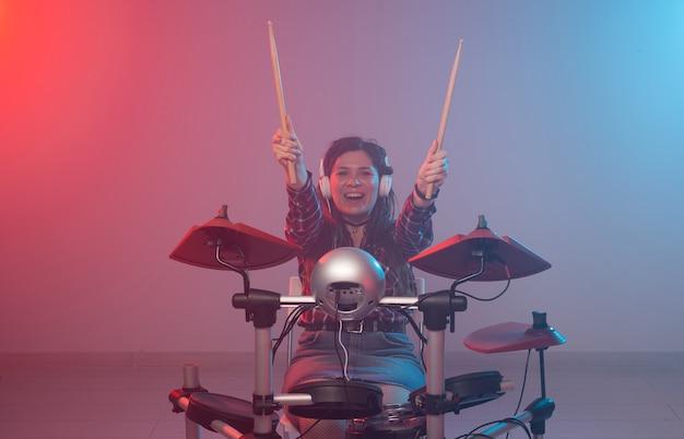 Concepto de música, batería y hobby - mujer joven tocando la batería electrónica en el club