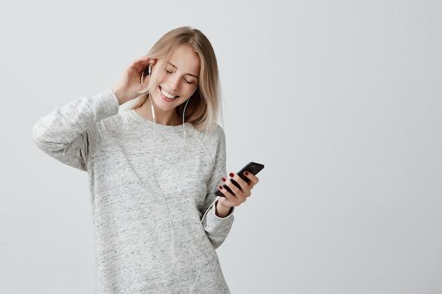 Concepto de música, felicidad y tecnología. la encantadora mujer adolescente tiene el cabello teñido de rubio, escucha música en el teléfono celular y baila alegremente