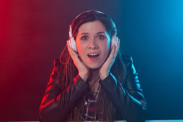 Concepto de música, meloman y personas: una mujer feliz escuchando música y disfrutándola.
