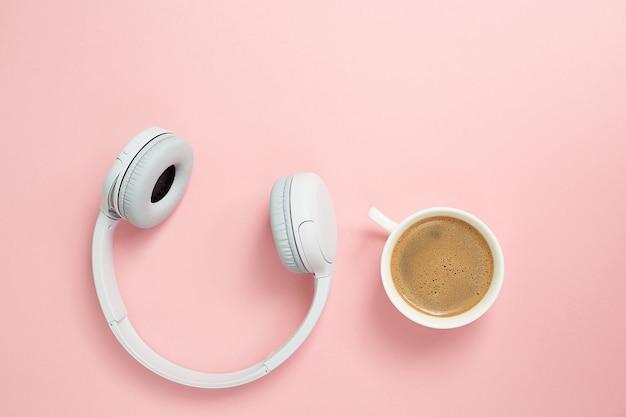 Concepto de música o podcast con auriculares y una taza de café en la mesa rosa, endecha plana. vista superior, endecha plana