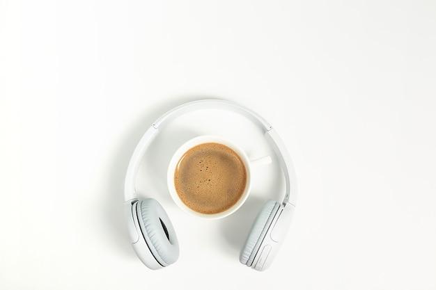 Concepto de música o podcast con auriculares y taza de café. vista superior, endecha plana