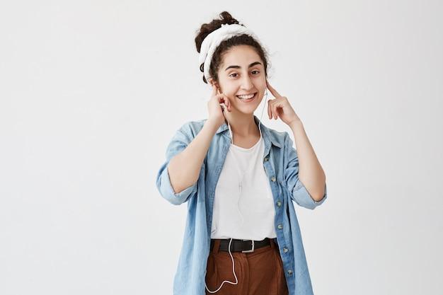 Concepto de música y tecnología. chica de cabello oscuro escuchando audiolibros o radio en el teléfono celular con auriculares, mirando y sonriendo contra la pared del espacio de copia blanca para contenido publicitario