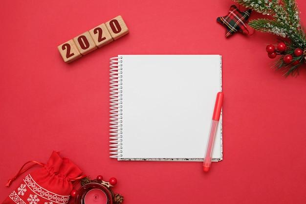 Concepto de navidad y año nuevo 2020, cubos de madera y decoraciones en rojo