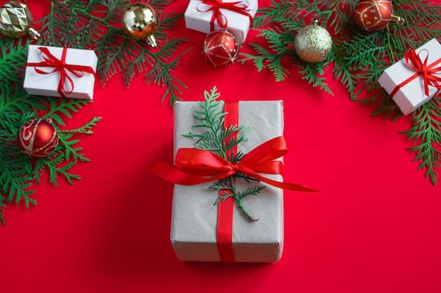 Concepto de navidad y año nuevo. cajas de regalo y decoración sobre un fondo rojo.