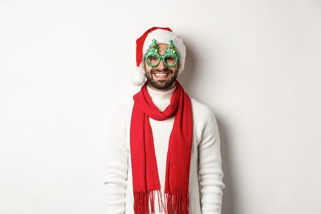 Concepto de navidad, año nuevo y celebración. hombre feliz riendo, vistiendo gorro de papá noel y gafas de fiesta, de pie sobre fondo blanco.