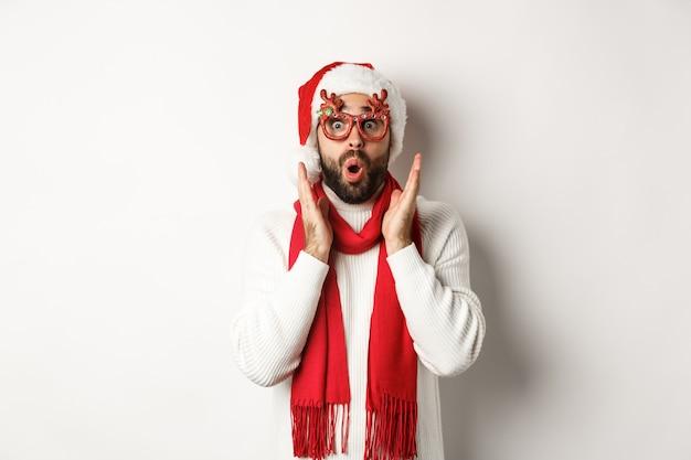 Concepto de navidad, año nuevo y celebración. hombre con gafas de fiesta y gorro de papá noel mirando sorprendido, escuchar oferta comercial, de pie sobre fondo blanco.