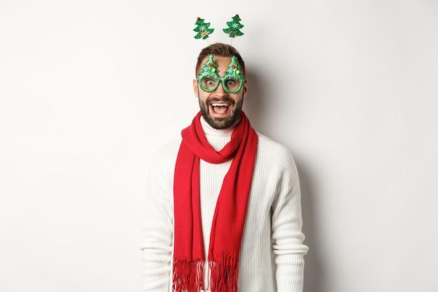 Concepto de navidad, año nuevo y celebración. hombre guapo con barba que parece sorprendido, con gafas de fiesta y accesorios, fondo blanco.