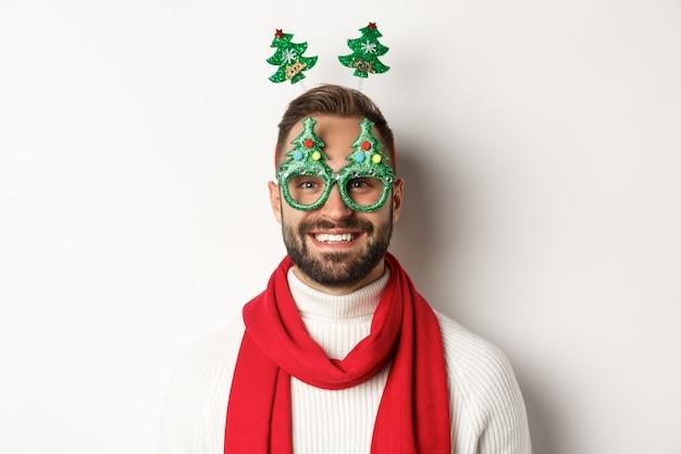 Concepto de navidad, año nuevo y celebración. primer plano de hombre guapo con barba en gafas de fiesta divertidas mirando feliz, de pie contra el fondo blanco.