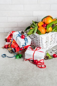 Concepto de navidad y año nuevo mandarinas frescas con hojas verdes en una cesta blanca decoración navideña y cajas de regalo en mesa gris