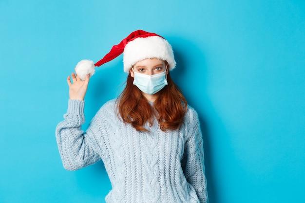 Concepto de navidad, cuarentena y covid-19. chica pelirroja con mascarilla y jugando con gorro de papá noel, celebrando el año nuevo en el encierro, de pie sobre fondo azul.