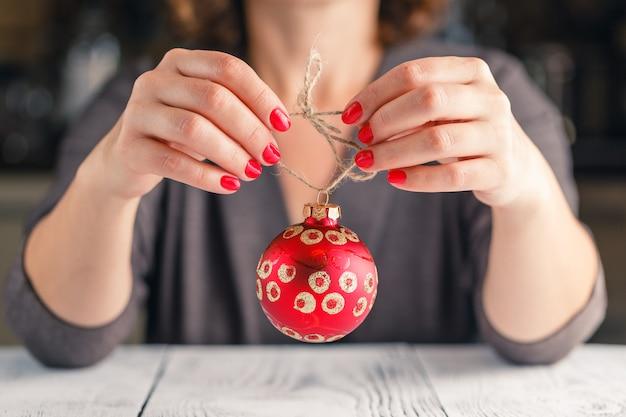 Concepto de navidad, decoración, vacaciones y personas - cerca de la mano de mujer sosteniendo la bola roja de navidad