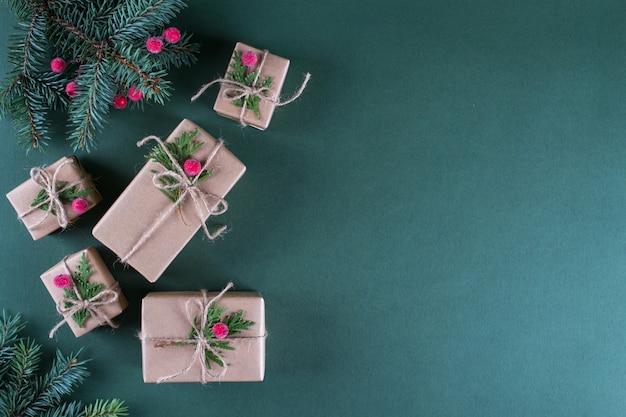 Concepto de navidad embalaje de regalos en papel artesanal beige vintage y decoración natural. ramas de abeto y frutos rojos. vista superior en plano