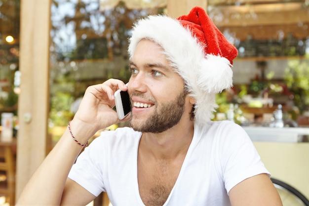 Concepto de navidad y felices fiestas. hombre joven atractivo con barba elegante con camiseta blanca y sombrero de santa claus hablando por teléfono móvil