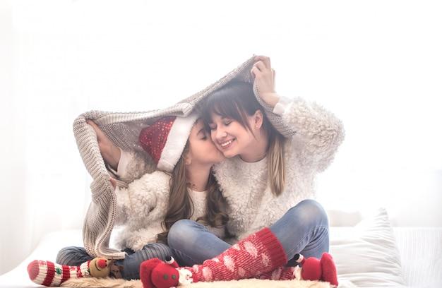 Concepto de navidad, mamá y su hija jugando