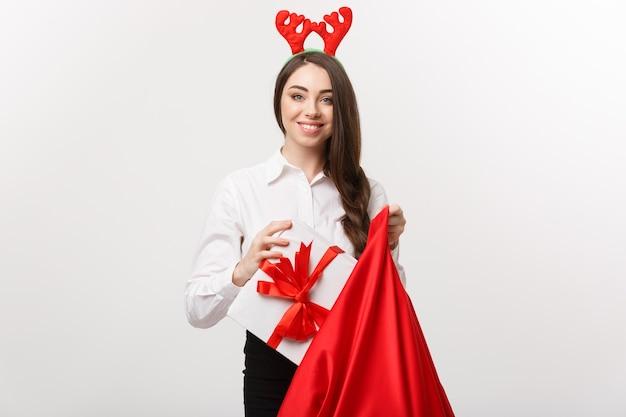 Concepto de navidad - mujer de negocios hermosa joven feliz con presente en bolsa de santa.