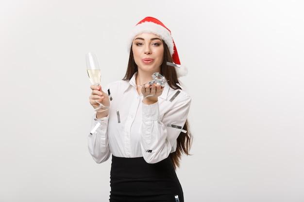 Concepto de navidad - mujer de negocios joven sosteniendo champán y confeti que sopla.