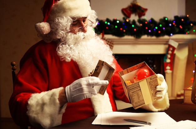 Concepto de navidad. santa claus hace juguetes, de cerca. adornos navideños en mesa de madera