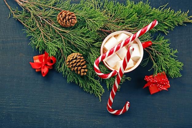 Concepto de navidad. taza de chocolate caliente con malvaviscos y adornos de mesa de madera