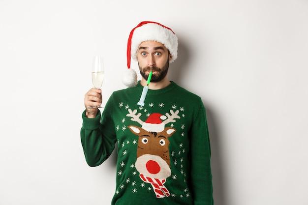 Concepto de navidad y vacaciones. chico divertido con gorro de papá noel que sopla un silbato de fiesta, bebiendo champán, de pie sobre fondo blanco.