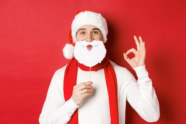 Concepto de navidad, vacaciones de invierno y celebración. hombre guapo complacido con gorro de papá noel, sosteniendo una larga máscara de barba blanca y mostrando un signo bien, de pie sobre fondo rojo