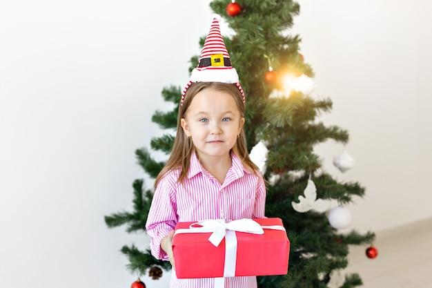 Concepto de navidad y vacaciones - niño feliz con caja de regalo sobre fondo de árbol de navidad.