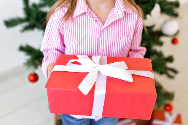Concepto de navidad y vacaciones - primer plano de niño con caja de regalo sobre fondo de árbol de navidad.