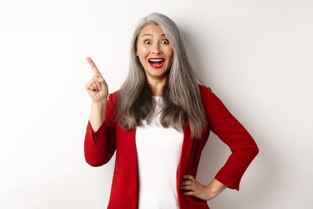 Concepto de negocio. alegre empresaria asiática con cabello gris, vestido con blazer rojo y maquillaje, apuntando hacia la esquina superior izquierda y sonriendo asombrado, fondo blanco.