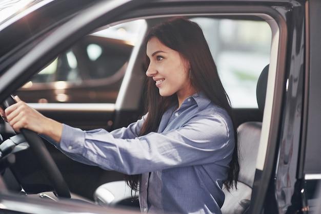 Concepto de negocio de automóviles, venta de automóviles, consumo y personas: mujer feliz que toma la llave del automóvil del concesionario en el salón del automóvil