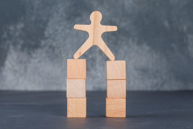 Concepto de negocio con bloques de madera con figura humana de madera.