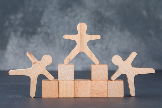 Concepto de negocio con bloques de madera con figuras humanas de madera.