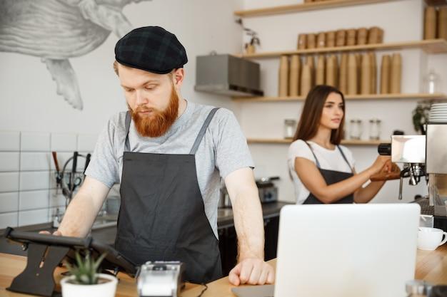 Concepto de negocio del café - el barman barbudo hermoso joven, el barista o el encargado que fijan la orden de huésped en menú digital de la tablilla en la cafetería moderna.