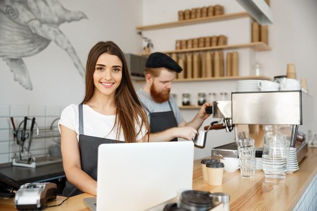 Concepto de negocio de café - caucásico barista barista o gerente de trabajo y cepillado en la computadora portátil en la cafetería moderna.