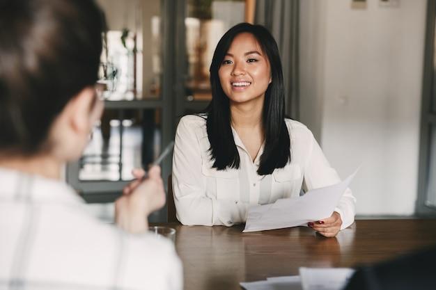 Concepto de negocio, carrera y colocación: alegre mujer asiática sonriendo y sosteniendo un currículum, mientras está sentada frente a los directores durante una reunión corporativa o una entrevista de trabajo