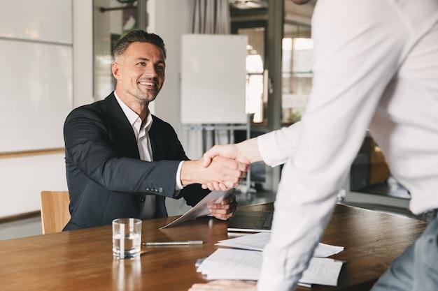 Concepto de negocio, carrera y colocación: director satisfecho de 30 años sonriendo y dándose la mano con el candidato masculino, que fue reclutado durante una entrevista en la oficina