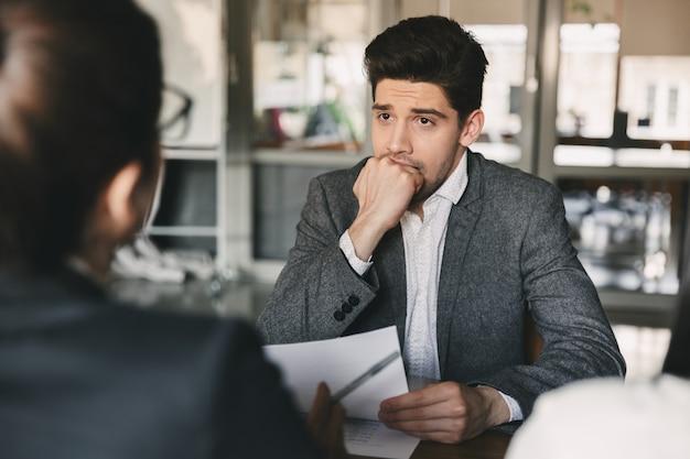 Concepto de negocio, carrera y colocación: hombre europeo de 30 años mordiendo el puño y preocupándose durante la entrevista de trabajo en la oficina, con un grupo de especialistas