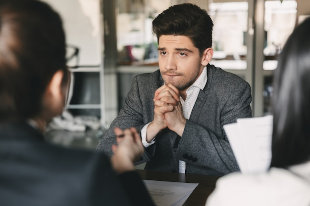 Concepto de negocio, carrera y colocación: hombre nervioso y tenso de 30 años que se preocupa y junta los puños durante la entrevista de trabajo en la oficina, con un colectivo de especialistas