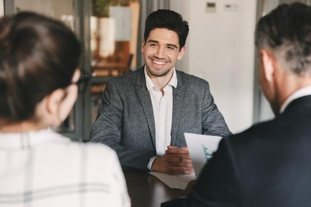 Concepto de negocio, carrera y colocación: joven caucásico sonriendo, sentado frente a los directores durante una reunión corporativa o una entrevista de trabajo