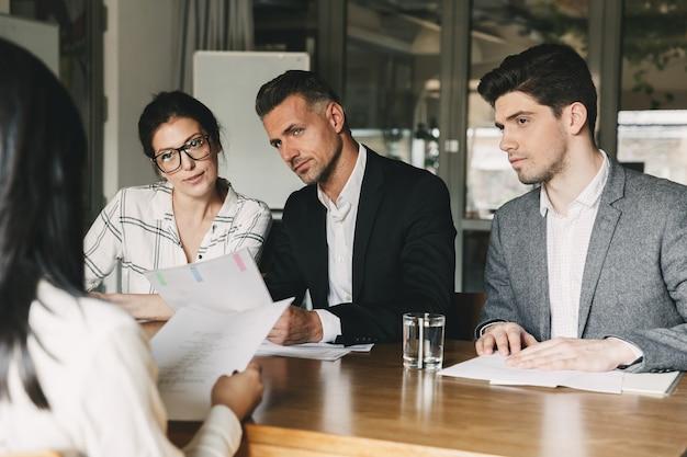 Concepto de negocio, carrera y colocación: junta directiva de una empresa internacional sentada a la mesa en la oficina y entrevistando a una mujer para el personal