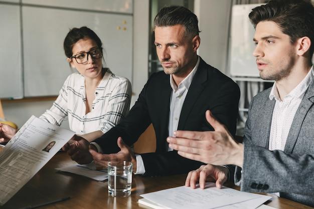 Concepto de negocio, carrera y colocación: junta directiva sentada a la mesa en la oficina y examinando el currículum de la trabajadora durante la reunión corporativa