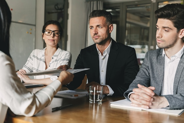 Concepto de negocio, carrera y colocación: junta directiva sentada a la mesa en la oficina y examinando el currículum de la trabajadora durante la reunión