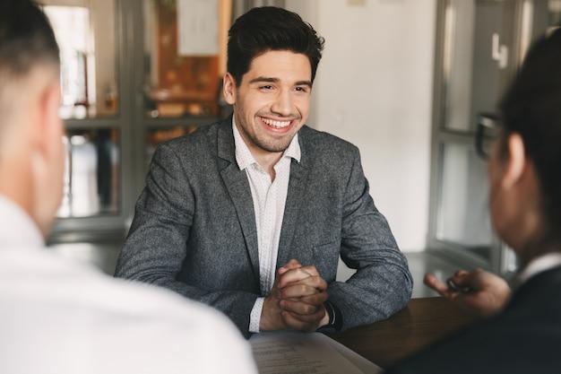 Concepto de negocio, carrera y colocación - sonriente hombre caucásico de 30 años negociando con empleados de gran empresa, durante la entrevista de trabajo en la oficina