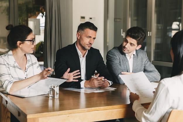 Concepto de negocio, carrera y colocación: tres directores ejecutivos o gerentes en jefe sentados a la mesa en la oficina y discutiendo el trabajo con personal nuevo durante la entrevista