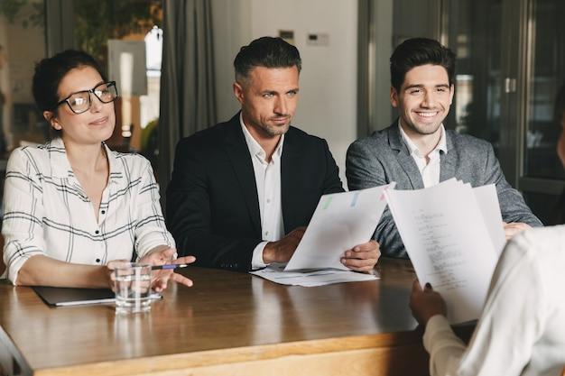 Concepto de negocio, carrera y colocación: tres directores ejecutivos o gerentes en jefe sentados a la mesa en la oficina y entrevistando a una mujer durante la reunión