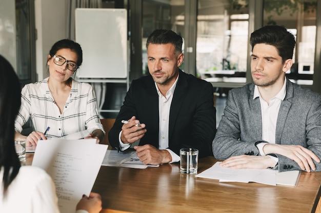 Concepto de negocio, carrera y colocación: tres directores ejecutivos o gerentes en jefe sentados a la mesa en la oficina y entrevistando a una mujer para un trabajo en la empresa