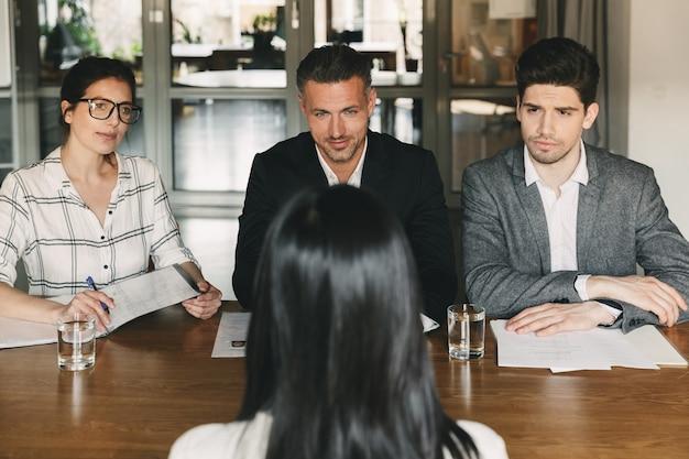 Concepto de negocio, carrera y contratación: grupo de empleadores en ropa formal sentados a la mesa en la oficina y entrevistando a una mujer para un trabajo en una gran empresa