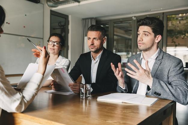 Concepto de negocio, carrera y ubicación: tres directores ejecutivos o gerentes en jefe sentados a la mesa en la oficina y negociando con el nuevo personal durante la entrevista