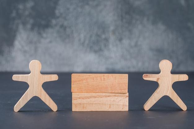 Concepto de negocio con columna de bloques de madera con figura humana de madera.